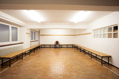 Man sitting in empty locker room Stock Photos