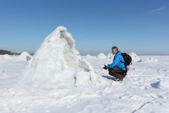 Man sitting at the entrance an igloo  in on a snowy reservoir. Man sitting at the entrance an igloo on a snowy reservoir inon a snowy reservoir, Novosibirsk Stock Photo