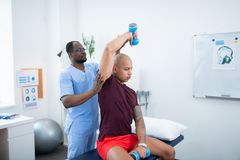 Man sitting and exercising with barbells visiting therapist. Exercising with barbells. Tattooed young bald men sitting and exercising with barbells visiting royalty free stock photo