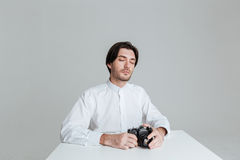 Man sitting with eyes closed. Young bristled man with eyes closed sitting at the table with eyes closed isolated on the gray background royalty free stock photos