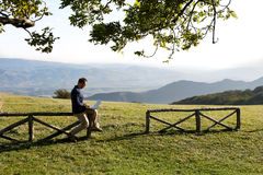 Man sitting on fence in countryside using laptop Royalty Free Stock Photos