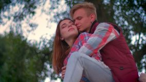 Man is sitting on fence while his girlfriend is standing near him, being held and looking ahead, green trees on. Background and summer park stock video