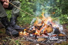 The man sitting by the fire in the forest. 