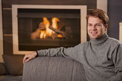 Man sitting by fireplace Stock Image