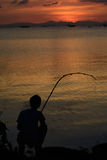 Man sitting fishing At sunset. Men Sitting Fishing A fishing rod in one hand. Sea at sunset Stock Photos