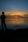 Man sitting on fishing At sunset. Men Standing Fishing A fishing rod in one hand. Sea at sunset Royalty Free Stock Photography