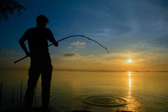 Man sitting on fishing At sunset. Men Standing Fishing A fishing rod in one hand. Sea at sunset Royalty Free Stock Image