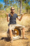 Man sitting on a flat tyre in the outback of Australia. Holding a jack stock photos