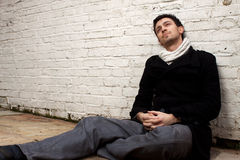 Man sitting on floor with back against wall. Handsome young man sitting down on a paved floor with his back against a white colored brick wall. He is wearing a royalty free stock photography