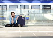Man sitting on floor with bag and talking on mobile phone Stock Image