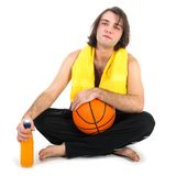 Man sitting on floor with basketball and orange juice, isolated at white Stock Image