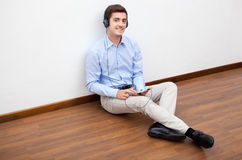 Man sitting on the floor with earphones Royalty Free Stock Images