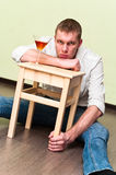 Man sitting on floor with glass of alcohol Stock Photos