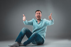 The man is sitting on the floor on gray background. Man showing different emotions. Stock Photo