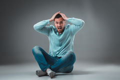 The man is sitting on the floor on gray background. Man showing different emotions. Royalty Free Stock Photography