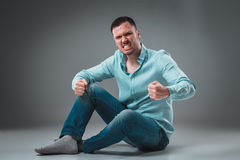 The man is sitting on the floor,  on gray background. Man showing different emotions. Stock Photos