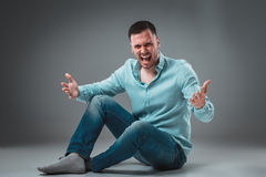 The man is sitting on the floor,  on gray background. Man showing different emotions. Royalty Free Stock Photos
