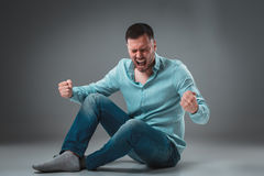 The man is sitting on the floor,  on gray background. Man showing different emotions. Royalty Free Stock Image