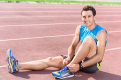 Man sitting on floor and lacing sneakers Royalty Free Stock Photo
