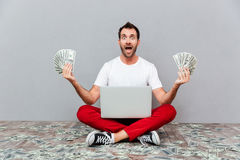 Man sitting on the floor with laptop and holding money Stock Image