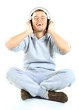 Man sitting on the floor listening to music Stock Images