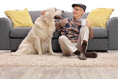 Man sitting on the floor and petting his dog Stock Image