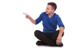 Man sitting  on the floor and pointing to side. Casual young man sitting  on the floor, looking and pointing to his side with a smile on his face. isolated on Royalty Free Stock Image