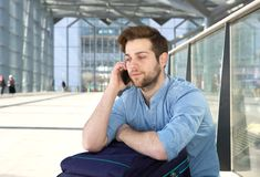 Man sitting on floor talking on mobile phone. Portrait of a handsome young man sitting on floor waiting for next flight and talking on mobile phone Stock Images