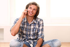 Man sitting on the floor and talking by phone Stock Image