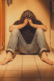 Man sitting on a floor tiles, sad, depressed and lonely Stock Photography