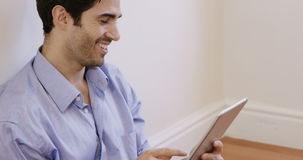 Man sitting on floor and using digital tablet. At home 4k stock video footage