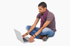 Man sitting on floor using laptop Stock Image