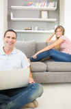 Man sitting on floor using laptop with woman listening to music Royalty Free Stock Photos
