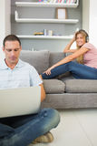 Man sitting on floor using laptop with woman listening to music Stock Images