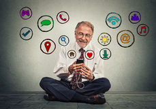 Man sitting on floor using texting on smartphone browsing web social media applications. Happy senior man sitting on floor using texting on smartphone browsing Stock Photos