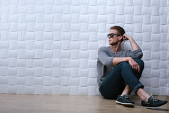 Man is sitting on the floor by the white wall. Man with a grey long-sleeve shirt on is sitting on the floor by the white wall and looking at something far Stock Photo