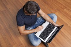 Man sitting on the floor working on laptop Stock Photos
