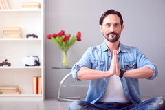 Man sitting on floor in yoga pose Stock Photography