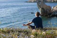 Man Sitting on Flower Fields Facing Ocean Stock Image