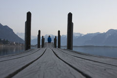 A man sitting footbridge over the water Stock Photo