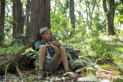 Man sitting in the forest under the tree. Young asian man sitting in the forest under the tree with backpack Royalty Free Stock Image