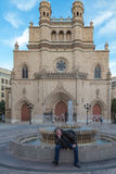 Man sitting on a fountain in front of the cathedral of Castelló Royalty Free Stock Images