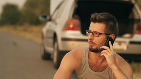 Man sitting in a front of broken with cell phone. Road trip car trouble. A young man with a silver car that broke down on the road stock footage