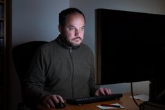 Man sitting in front of computer at night Royalty Free Stock Photo