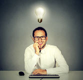 Man sitting in front of keyboard with light bulb over head Royalty Free Stock Photography