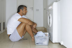 Man sitting in front of a washing machine. Royalty Free Stock Photo