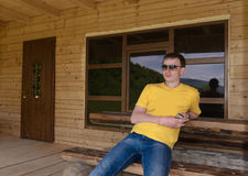 Man sitting in front of a wooden cabin Stock Photo