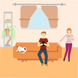 Man sitting with gadget on couch and woman standing near the couch at their home. With cat sleeping on couch Stock Image
