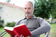 Man sitting in garden and reading a book Stock Photography