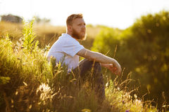 Man sitting on the grass in the evening Stock Photo